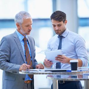 Geschäftsleute analysieren mögliche Seminare auf einem Tablet