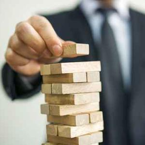 Geschäftsmann setzt letzten Baustein auf einem Turm - Wachstumskonzept