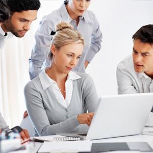 Geschäftsfrau zeigt Ihren Kollegen Seminare auf dem Laptop